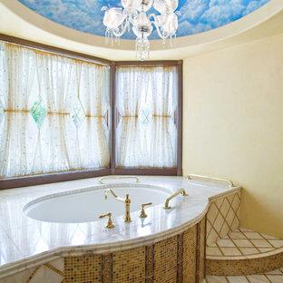 Imagen de cuarto de baño mediterráneo con bañera encastrada sin remate, baldosas y/o azulejos multicolor, baldosas y/o azulejos en mosaico, paredes amarillas y suelo de madera oscura