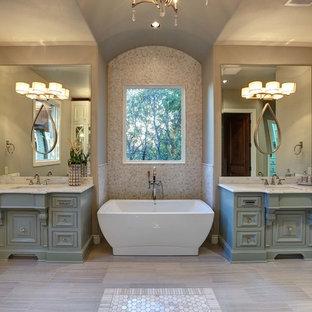 Foto di una stanza da bagno padronale classica di medie dimensioni con ante con bugna sagomata, ante turchesi, vasca freestanding, pareti beige, pavimento in gres porcellanato, top in marmo, piastrelle beige, piastrelle a mosaico e lavabo sottopiano