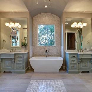 Bild på ett mellanstort vintage en-suite badrum, med luckor med upphöjd panel, turkosa skåp, ett fristående badkar, beige kakel, mosaik, beige väggar, klinkergolv i porslin, ett undermonterad handfat och marmorbänkskiva