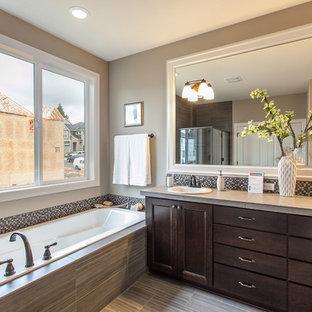 Imagen de cuarto de baño principal, tradicional renovado, de tamaño medio, con lavabo encastrado, armarios con paneles empotrados, puertas de armario de madera en tonos medios, encimera de azulejos, ducha empotrada, sanitario de pared, baldosas y/o azulejos beige, baldosas y/o azulejos de porcelana, paredes beige y suelo de baldosas de porcelana