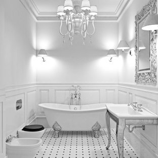 Example of a mid-sized ornate 3/4 white tile and ceramic tile ceramic tile and white floor claw-foot bathtub design in Orange County with furniture-like cabinets, white cabinets, a one-piece toilet, white walls, a drop-in sink and solid surface countertops
