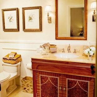 Ejemplo de cuarto de baño principal, tradicional, pequeño, con lavabo bajoencimera, armarios tipo mueble, puertas de armario de madera oscura, encimera de ónix, combinación de ducha y bañera, sanitario de una pieza, paredes blancas y suelo de piedra caliza