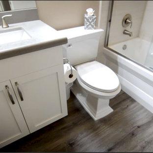 Idée de décoration pour une petit salle de bain minimaliste pour enfant avec un placard à porte shaker, des portes de placard blanches, une baignoire en alcôve, un combiné douche/baignoire, un WC séparé, un carrelage beige, des carreaux de porcelaine, un mur beige, sol en stratifié, un lavabo encastré, un plan de toilette en quartz modifié, un sol beige, une cabine de douche à porte coulissante et un plan de toilette gris.