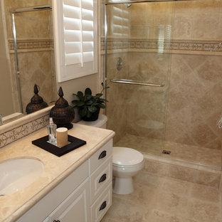 Ispirazione per una piccola stanza da bagno tradizionale con ante con bugna sagomata, ante bianche, WC a due pezzi, piastrelle beige, piastrelle in travertino, pareti beige, pavimento in travertino, lavabo sottopiano, pavimento beige, porta doccia scorrevole e doccia alcova
