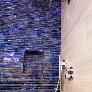 Imagen de cuarto de baño con ducha, contemporáneo, de tamaño medio, con lavabo bajoencimera, armarios con paneles lisos, puertas de armario de madera en tonos medios, encimera de cuarzo compacto, ducha empotrada, sanitario de dos piezas, baldosas y/o azulejos grises, baldosas y/o azulejos de vidrio laminado, paredes azules y suelo de baldosas de porcelana