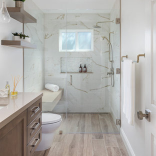 This is an example of a transitional 3/4 bathroom in Orange County with beaded inset cabinets, medium wood cabinets, a curbless shower, multi-coloured tile, white walls, wood-look tile, an undermount sink, brown floor, a hinged shower door, beige benchtops, a niche, a shower seat, a single vanity and a built-in vanity.