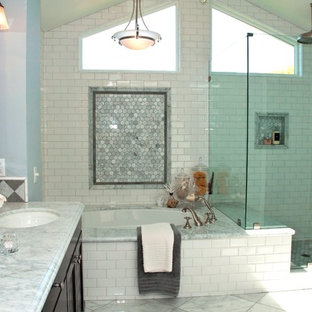 Example of a large transitional master white tile and subway tile marble floor and white floor corner shower design in Orange County with furniture-like cabinets, dark wood cabinets, an undermount sink, marble countertops, a hinged shower door, blue walls, an undermount tub and white countertops