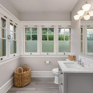 Ejemplo de cuarto de baño infantil, tradicional renovado, de tamaño medio, con armarios con paneles empotrados, ducha esquinera, sanitario de pared, baldosas y/o azulejos marrones, baldosas y/o azulejos de porcelana, paredes grises, suelo con mosaicos de baldosas, lavabo bajoencimera, encimera de mármol, puertas de armario grises y bañera exenta