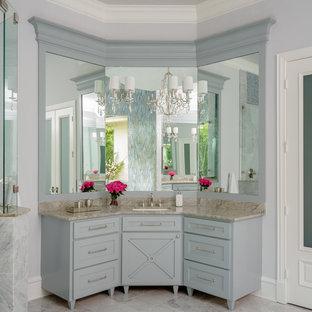 Modelo de cuarto de baño principal, clásico renovado, grande, con armarios estilo shaker, paredes grises, lavabo bajoencimera, puertas de armario grises, bañera exenta, ducha esquinera, suelo de mármol, encimera de cuarcita, suelo blanco, ducha con puerta con bisagras y encimeras grises