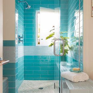 Ispirazione per una stanza da bagno costiera con piastrelle blu, doccia alcova, ante lisce, ante in legno bruno, vasca ad alcova, piastrelle di vetro, pareti bianche, parquet chiaro, top in legno e porta doccia a battente