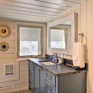 Imagen de cuarto de baño rural, de tamaño medio, con armarios con paneles empotrados, puertas de armario azules, paredes blancas, suelo de baldosas de cerámica, encimera de cuarzo compacto, suelo negro y encimeras grises