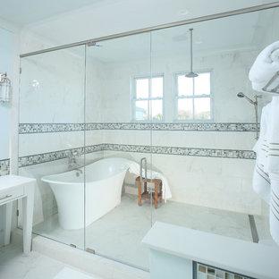 Foto på ett stort vintage en-suite badrum, med möbel-liknande, vita skåp, ett fristående badkar, våtrum, flerfärgad kakel, vit kakel, marmorkakel, vita väggar, marmorgolv, vitt golv och dusch med gångjärnsdörr