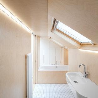 Foto di una stanza da bagno minimal con lavabo sospeso, vasca da incasso, pareti beige e pavimento con piastrelle in ceramica
