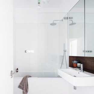 Modern bathroom in London with an alcove bath, a shower/bath combination, white tiles, white walls, a wall-mounted sink, grey floors, an open shower and a single sink.