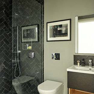 Inspiration for an eclectic wet room in London with black cabinets, a wall mounted toilet, marble tiles, grey walls, ceramic flooring, a wall-mounted sink, solid surface worktops and black floors.