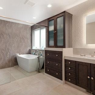 シアトルの中くらいのトランジショナルスタイルのおしゃれなマスターバスルーム (濃色木目調キャビネット、置き型浴槽、グレーのタイル、磁器タイル、磁器タイルの床、アンダーカウンター洗面器、珪岩の洗面台、開き戸のシャワー、落し込みパネル扉のキャビネット、洗い場付きシャワー、ベージュの床、ベージュのカウンター) の写真