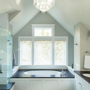 Klassisk inredning av ett mellanstort svart svart en-suite badrum, med skåp i shakerstil, vita skåp, ett undermonterat badkar, en dusch i en alkov, vit kakel, tunnelbanekakel, svarta väggar, klinkergolv i porslin, ett undermonterad handfat, bänkskiva i täljsten, svart golv och dusch med gångjärnsdörr