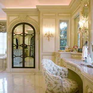 Photo of an expansive mediterranean ensuite bathroom in Dallas with freestanding cabinets, light wood cabinets, granite worktops, an alcove bath, white tiles, stone tiles, beige walls and limestone flooring.