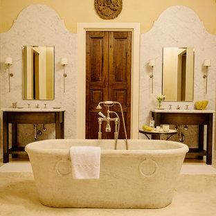 Imagen de cuarto de baño principal, mediterráneo, extra grande, con armarios abiertos, puertas de armario de madera en tonos medios, bañera exenta, baldosas y/o azulejos grises, baldosas y/o azulejos de piedra, paredes amarillas, suelo de mármol, encimera de mármol y lavabo bajoencimera