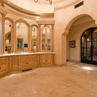 フェニックスの巨大な地中海スタイルのおしゃれなマスターバスルーム (家具調キャビネット、茶色いキャビネット、置き型浴槽、アルコーブ型シャワー、一体型トイレ、マルチカラーのタイル、ミラータイル、マルチカラーの壁、トラバーチンの床、ベッセル式洗面器、御影石の洗面台、マルチカラーの床、オープンシャワー、マルチカラーの洗面カウンター) の写真