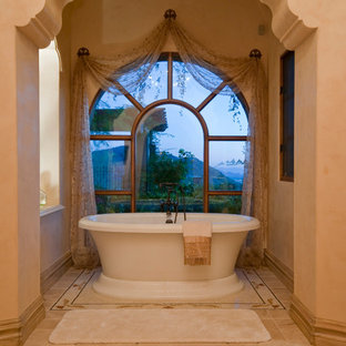 Design ideas for an expansive mediterranean ensuite bathroom in Phoenix with freestanding cabinets, brown cabinets, a freestanding bath, an alcove shower, a one-piece toilet, multi-coloured tiles, mirror tiles, multi-coloured walls, travertine flooring, a vessel sink, granite worktops, multi-coloured floors, an open shower and multi-coloured worktops.