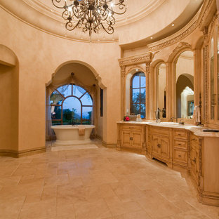 Photo of an expansive mediterranean ensuite bathroom in Phoenix with freestanding cabinets, brown cabinets, a freestanding bath, an alcove shower, a one-piece toilet, multi-coloured tiles, mirror tiles, multi-coloured walls, travertine flooring, a vessel sink, granite worktops, multi-coloured floors, an open shower and multi-coloured worktops.
