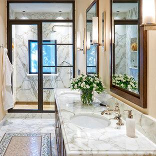 Diseño de cuarto de baño principal, mediterráneo, grande, con puertas de armario de madera oscura, ducha empotrada, baldosas y/o azulejos blancos, baldosas y/o azulejos de mármol, paredes beige, suelo de mármol, lavabo bajoencimera, encimera de mármol, suelo blanco, ducha con puerta con bisagras, encimeras blancas y armarios con paneles con relieve