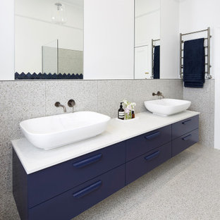 Photo of a large contemporary kids bathroom in Melbourne with flat-panel cabinets, blue cabinets, a freestanding tub, an open shower, a wall-mount toilet, gray tile, multi-coloured walls, terrazzo floors, a vessel sink, engineered quartz benchtops, multi-coloured floor, an open shower and white benchtops.