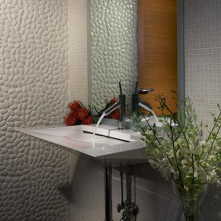 Modern inredning av ett litet badrum med dusch, med öppna hyllor, en toalettstol med hel cisternkåpa, grå kakel, mosaik, flerfärgade väggar, marmorgolv, ett väggmonterat handfat och grönt golv