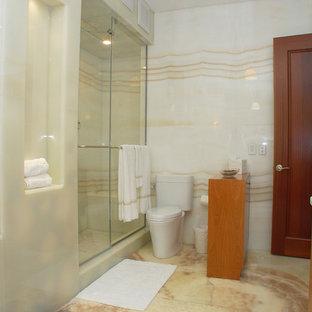 Idées déco pour une grand salle de bain principale moderne avec un placard à porte plane, des portes de placard en bois clair, une baignoire d'angle, une douche d'angle, un WC séparé, un carrelage multicolore, des dalles de pierre, un mur multicolore, un sol en marbre, une vasque, un plan de toilette en onyx, un sol multicolore et une cabine de douche à porte coulissante.