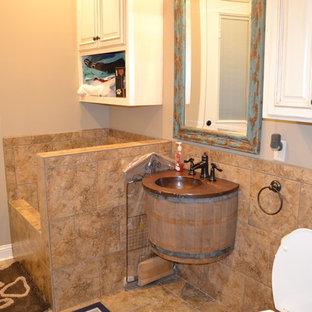 На фото: ванная комната среднего размера в стиле рустика с фасадами с выступающей филенкой, искусственно-состаренными фасадами, раздельным унитазом, керамической плиткой, монолитной раковиной, столешницей из меди, бежевыми стенами, полом из травертина и бежевым полом с