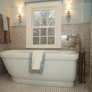 Elegant beige tile and subway tile porcelain floor freestanding bathtub photo in Minneapolis with blue walls
