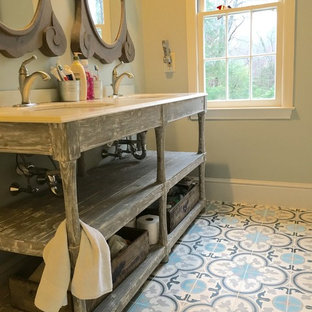 Modelo de cuarto de baño principal, de estilo de casa de campo, de tamaño medio, con armarios abiertos, puertas de armario con efecto envejecido, baldosas y/o azulejos azules, baldosas y/o azulejos grises, baldosas y/o azulejos blancos, baldosas y/o azulejos de cemento, paredes grises, suelo de cemento, encimera de mármol y lavabo bajoencimera