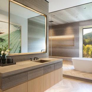 Foto på ett mycket stort rustikt grå en-suite badrum, med släta luckor, skåp i mellenmörkt trä, ett fristående badkar, grå kakel, grå väggar, ett nedsänkt handfat, bänkskiva i akrylsten och beiget golv