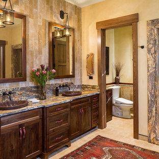 Foto på ett stort rustikt en-suite badrum, med stenkakel, skåp i shakerstil, skåp i mörkt trä, en dusch i en alkov, en toalettstol med hel cisternkåpa, beige väggar, kalkstensgolv, ett fristående handfat, granitbänkskiva, beiget golv och med dusch som är öppen