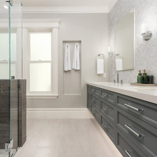 Inspiration for a large transitional master gray tile and marble tile ceramic tile and beige floor walk-in shower remodel in San Francisco with beaded inset cabinets, gray cabinets, a one-piece toilet, gray walls, an undermount sink, quartz countertops and a hinged shower door