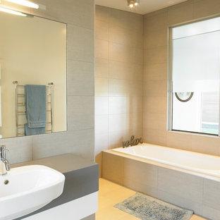 Imagen de cuarto de baño principal, actual, grande, con armarios con paneles lisos, puertas de armario grises, baldosas y/o azulejos beige, baldosas y/o azulejos de cemento, paredes beige, suelo de azulejos de cemento, lavabo suspendido, encimera de cemento, suelo amarillo y encimeras grises