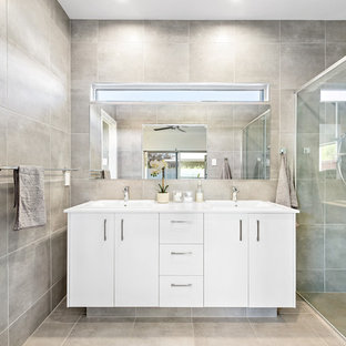 Inspiration for a contemporary master bathroom in Sunshine Coast with flat-panel cabinets, white cabinets, a curbless shower, gray tile, grey walls, grey floor and white benchtops.