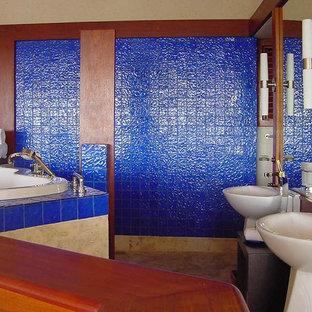 Ejemplo de cuarto de baño principal, tropical, extra grande, con baldosas y/o azulejos de vidrio, lavabo con pedestal, puertas de armario de madera oscura, encimera de madera, jacuzzi, baldosas y/o azulejos azules, paredes azules y suelo de travertino