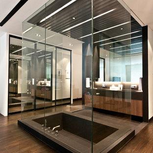 Ispirazione per una stanza da bagno padronale contemporanea con ante lisce, ante in legno chiaro, vasca sottopiano, piastrelle marroni, pareti marroni e pavimento in legno massello medio