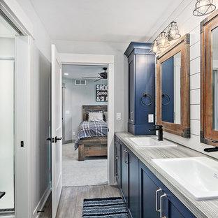 Imagen de cuarto de baño con ducha, campestre, con armarios estilo shaker, bañera exenta, ducha empotrada, sanitario de dos piezas, paredes blancas, suelo vinílico, lavabo encastrado, encimera de cuarzo compacto, suelo gris, ducha con puerta con bisagras, encimeras grises y puertas de armario azules