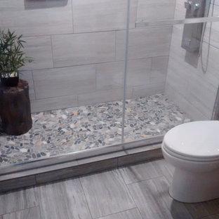 Esempio di una stanza da bagno padronale costiera di medie dimensioni con doccia alcova, WC a due pezzi, piastrelle grigie, piastrelle in ceramica, pavimento con piastrelle in ceramica, lavabo integrato, pavimento grigio e porta doccia scorrevole