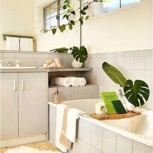 Foto di una piccola stanza da bagno padronale stile marinaro con ante grigie, vasca ad angolo, piastrelle grigie, piastrelle di cemento, pareti bianche, pavimento in linoleum, lavabo integrato e top in laminato