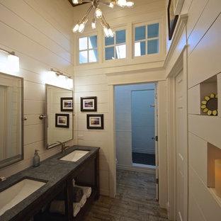 Modelo de cuarto de baño infantil, clásico renovado, pequeño, con lavabo bajoencimera, armarios abiertos, puertas de armario con efecto envejecido, encimera de esteatita, ducha abierta, baldosas y/o azulejos blancos, baldosas y/o azulejos de cerámica, paredes blancas y suelo de baldosas de porcelana