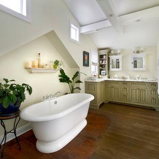 Diseño de cuarto de baño principal, tradicional, grande, con bañera exenta, suelo de madera oscura, lavabo bajoencimera, encimera de mármol, armarios con puertas mallorquinas, puertas de armario verdes, paredes amarillas y ducha a ras de suelo