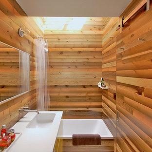 Diseño de cuarto de baño principal, asiático, de tamaño medio, con lavabo bajoencimera, armarios con paneles lisos, bañera encastrada, combinación de ducha y bañera, paredes marrones, encimera de cuarcita, puertas de armario amarillas y ducha con cortina