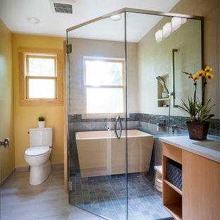 Foto de cuarto de baño principal, de estilo zen, de tamaño medio, con armarios con paneles lisos, puertas de armario de madera clara, baldosas y/o azulejos grises, encimera de cuarzo compacto, encimeras blancas, bañera exenta, ducha esquinera, sanitario de dos piezas, baldosas y/o azulejos de pizarra, paredes blancas, suelo de baldosas de porcelana, lavabo bajoencimera, suelo gris y ducha con puerta con bisagras