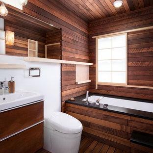 Modelo de cuarto de baño de estilo zen, de tamaño medio, con armarios con paneles lisos, puertas de armario de madera en tonos medios, bañera encastrada sin remate, sanitario de pared, paredes blancas, suelo de madera oscura, lavabo integrado y suelo marrón