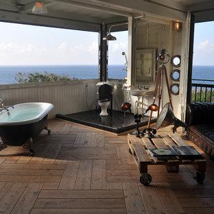 Imagen de cuarto de baño de estilo zen, grande, con bañera exenta, ducha abierta, baldosas y/o azulejos negros, suelo de madera clara y lavabo tipo consola