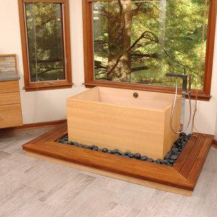 Ejemplo de cuarto de baño principal, asiático, de tamaño medio, con armarios con paneles lisos, puertas de armario de madera clara, bañera japonesa, paredes beige y encimera de cuarzo compacto